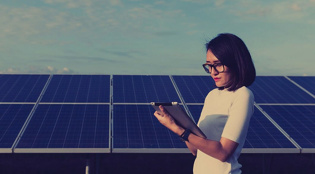 woman standing in front of solar panels and looking at iPad